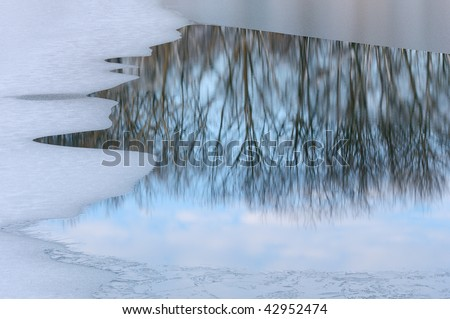 Abstract winter landscape of reflections of bare trees in lake water framed by ice, Michigan, USA - stock photo