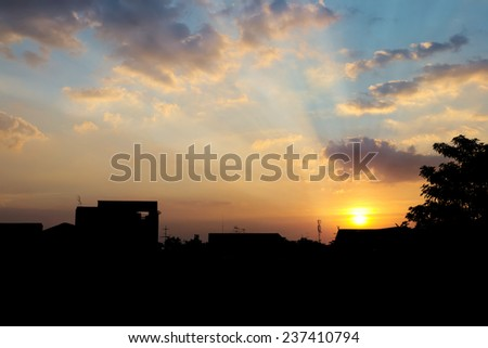 Abstract yellow cloudy sky with city silhouette in sunset hour background