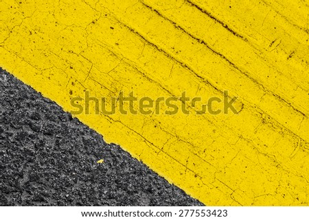 Abstract yellow road marking fragment with tire track relief on gray asphalt