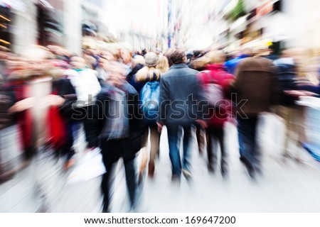 abstract zoom picture of a walking crowd in the shopping street of a city - stock photo