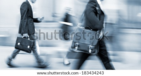 abstrakt image of business people in the street and modern style with a blurred background and blue tonality
