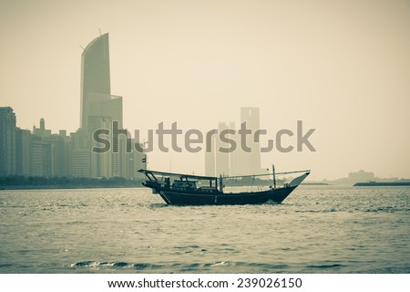 Abu Dhabi buildings skyline with old fishing boat on the front - stock photo