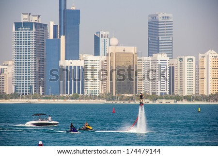 ABU DHABI - MARCH 31, 2013: Group of men doing water sports in front of skyline taken on March 31, 2013 in Abu Dhabi, United Arab Emirates.