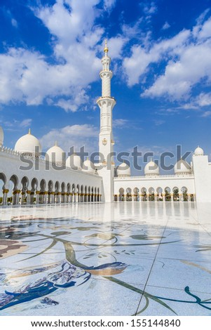 ABU DHABI, UAE - JUNE 11: The Sheikh Zayed Grand Mosque, muslims and tourists on June 11, 2013 in Abu Dhabi, UAE. It is the largest mosque in UAE and eighth largest mosque in world