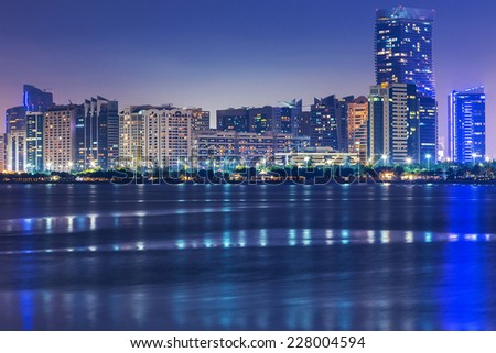 ABU DHABI, UAE - MARCH 28, 2014: Skyscrapers of Abu Dhabi at nightwith reflection in Persian Gulf, UAE. Abu Dhabi is the capital and the second most populous city of the United Arab Emirates - stock photo