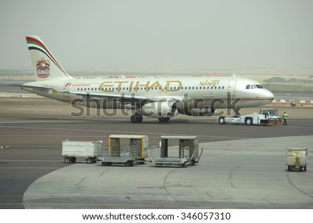 ABU DHABI, UAE - MARCH 10, 2015: Towing aircraft Airbus A320-232 (A6-EIR) Etihad Airways to the passenger terminal of Abu Dhabi airport - stock photo