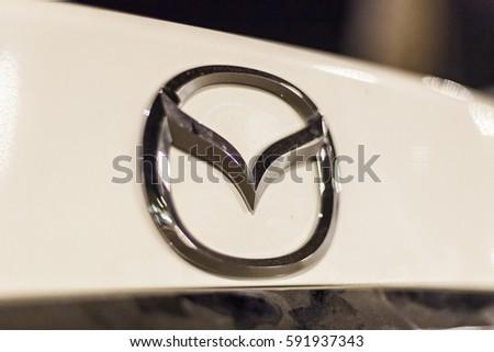 ABU DHABI, UAE - NOV 26, 2016: Mazda company logo on a car illuminated at night