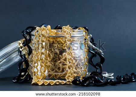 Abundance of fake gold, silver, pearls chains coming out of a glass jar.