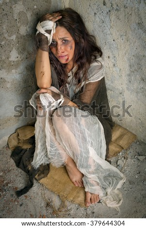 Abused and frightened woman sitting in the corner of a derelict building - stock photo
