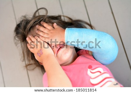 Abused little girl with a broken arm covering here face while crying. Concept photo of child abuse, violent in the family,domestic violent, social issues. - stock photo