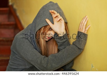 Abused teenage woman trying to hide and defend herself - stock photo