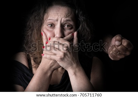 Abused woman victim of domestic violence, with man's fist.