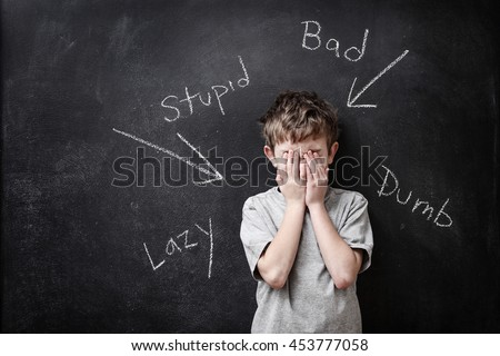 Abusive words written on a blackboard with a child covering his face - stock photo