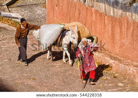 ABYANEH, IRAN - NOVEMBER 15, 2016: Man and woman traveling with a donkey in Abyaneh village.
