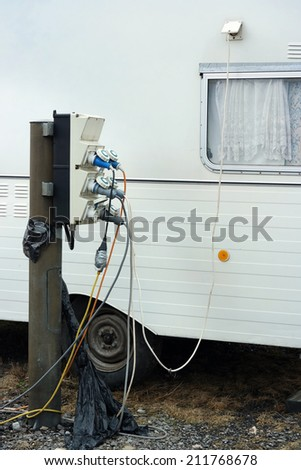 AC power sockets at a camping site in front of a connected caravan - stock photo