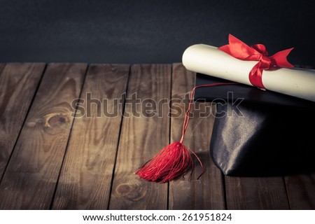 Academic. A diploma scroll tied with red ribbon, resting on a graduation mortarboard, on top of a wooden desk in front of a school blackboard.  Created in vintage style with low saturation. - stock photo