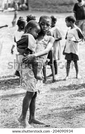 ACCARA, GHANA - MAR 6, 2012: Unidentified Ghanayan girl carries her little brother in the street in black and white. Children of Ghana suffer of poverty due to the unstable economical situation