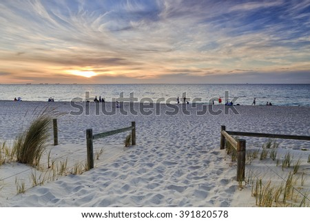 access and entrance to Cottesloe beach of Perth city in Western Australia on Indian coast. Relaxing people in a distance enjoying beautiful sunset over horizon and water.