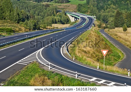 Access road to the highway between forests in the landscape, road sign right of way, in the middle of the highway electronic toll gates and bridges, view from above                                - stock photo