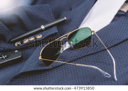 accessories, closeup sunglasses with gold frame on navy blue suit