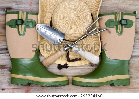 Accessories for a fashionable gardener with stylish rubber gumboots, a wide brimmed straw hat and crossed gardening utensils or tools - stock photo