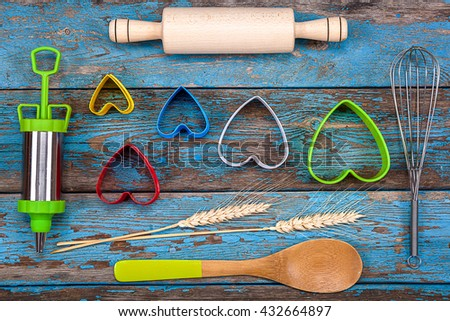 Accessories for baking. Cookie cutters, pastry syringe, whisk on a wooden background.