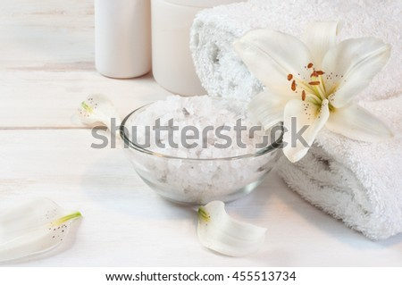 Accessories for bath (bath salt, towels, shampoo) decorated with white lily and its petals