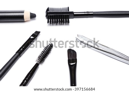 Accessories for care of the brows. Spooly brush, angle brushes, tweezers, brow comb / brush combo, black eyebrow pencil on white background. Eyebrow grooming tools - stock photo