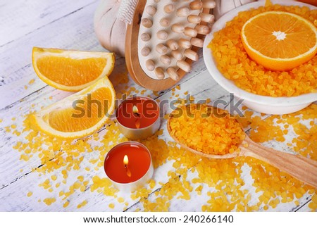 Accessories for massage therapy with candle light and bowl of bath salt on color wooden background - stock photo