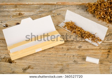 Accessories for rolling and smoking cigarettes on a rustic wooden table - stock photo