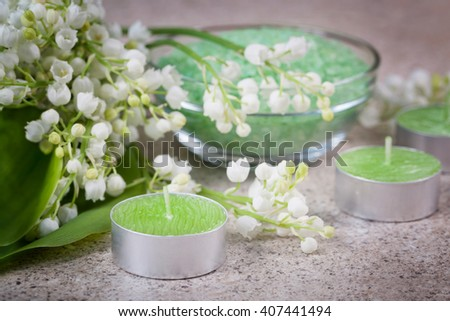 Accessories for spa. Lily of the valley flowers, bath salt and candles - stock photo