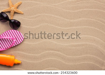Accessories for the beach lying on the sand - stock photo