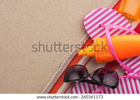 Accessories for the beach lying on the sand, with place for your text