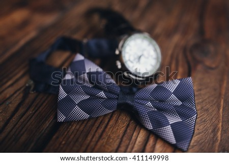 accessories groom on their wedding day.  Bow tie and a watch on a wooden table - stock photo