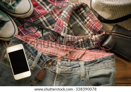 Accessory smart phone jeans Shoes,wallet, jeans, hats shirt on a wooden floor for trip - stock photo