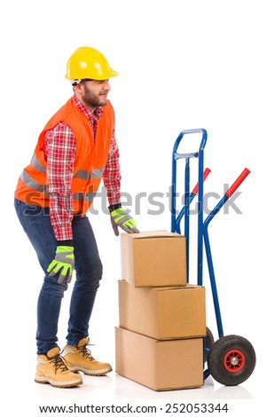Accident at work. Manual worker holding knee in pain. Full length studio shot isolated on white. - stock photo