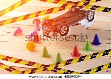 accident concept with toy car with police line on wooden floor with light flare effect - stock photo