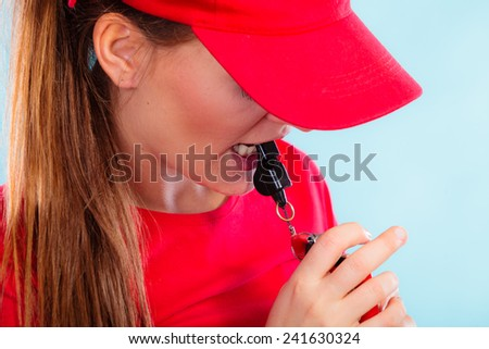 Accident prevention and water rescue. Closeup girl in red lifeguard outfit on duty blowing a whistle on blue - stock photo