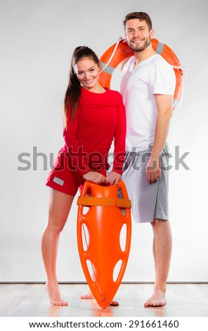 Accident prevention and water rescue. Full length man and woman lifeguard couple holding ring buoy float lifesaver equipment on gray - stock photo