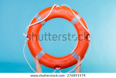 Accident prevention and water rescue. Life buoy ring lifebelt in female hands studio shot blue background - stock photo