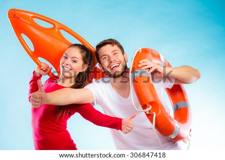 Accident prevention and water rescue. Man and woman lifeguard couple holding buoy lifesaver equipment giving thumb ub hand sign gesture on blue - stock photo