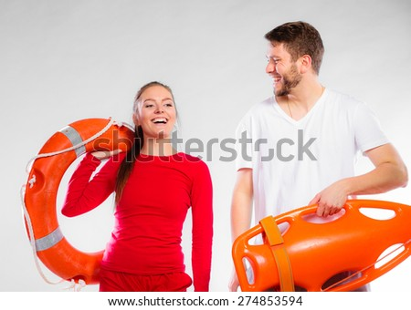 Accident prevention and water rescue. Young man and woman lifeguard couple on duty holding ring buoy float lifesaver equipment on gray - stock photo