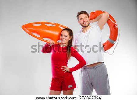 Accident prevention and water rescue. Young man and woman lifeguard couple on duty holding ring buoy float lifesaver equipment having fun on gray - stock photo
