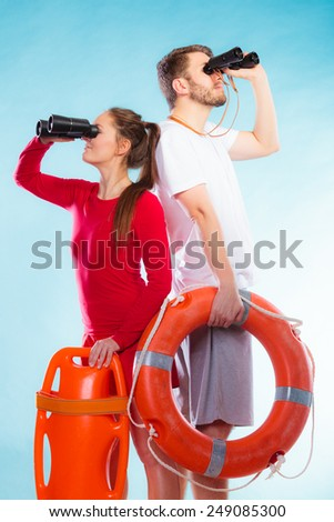 Accident prevention and water rescue. Young man and woman lifeguards on duty looking through binoculars keeping buoy lifesaver equipment on blue - stock photo