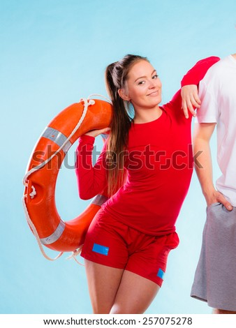 Accident prevention and water rescue. Young woman female smiling lifeguard on duty leaning on male arm holding lifesaver equipment on blue - stock photo