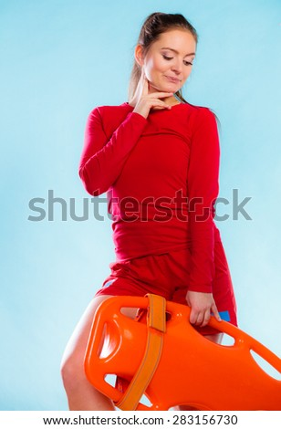 Accident prevention and water rescue. Young woman female thoughtful lifeguard on duty holding float lifesaver equipment on blue - stock photo
