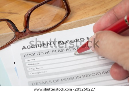 Accident report application form and human hand with pen on brown envelope and eyeglass, business insurance and risk concept; document is mock-up