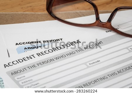 Accident report application form on brown envelope and eyeglass, business insurance and risk concept; document is mock-up - stock photo
