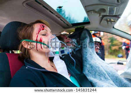 Accident - victim in a crashed vehicle, she receives medical first aid from firefighters - stock photo