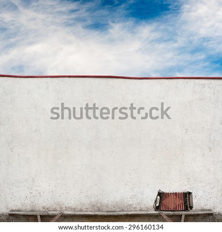 accordion on the bench near the wall, cloudy sky background - stock photo